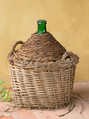 Antique old demijohn, carboy, by yellow wall. Wicker basket.