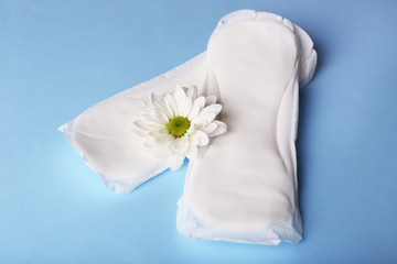 Sanitary pads and white flower on light blue background