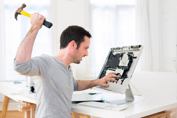 Young attractive man angry against computer