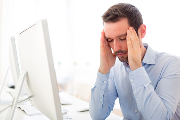 Young attractive man got a headache at the office