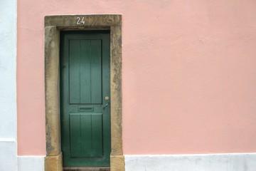 Hintergrund - rosa mediterrane Wand mit grüner Tür