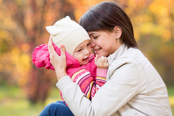 portrait of beautiful mother and kid girl outdoors in autumn par