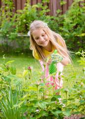 girl sprinkles rose in the garden