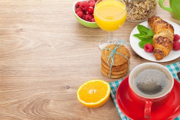 Healthy breakfast with muesli, berries, orange juice, coffee and