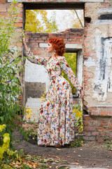 Red-head young woman near brick wall