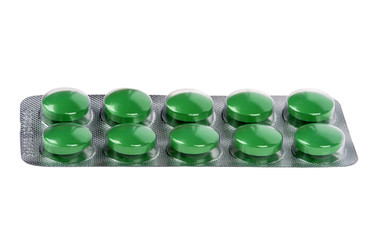 Green pills in blisters on white background