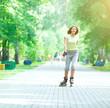 Roller skating sporty girl in park rollerblading on inline skate
