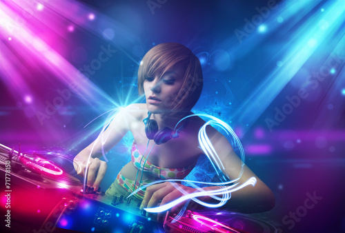 Energetic Dj girl mixing music with powerful light effects - 71778150
