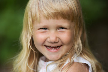 Happy little blonde girl cheerfully smiles