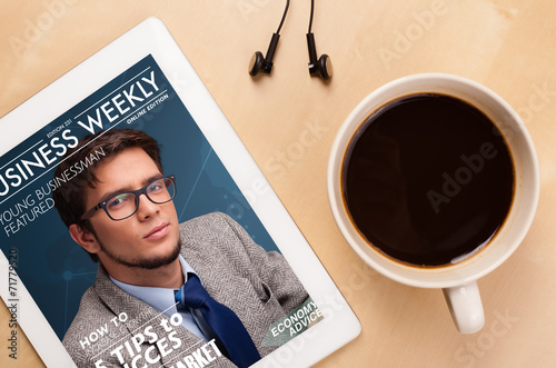 canvas print picture Tablet pc showing magazine on screen with a cup of coffee on a d