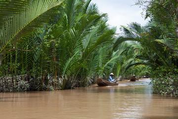 Vietnamese woman rowing a boat in Mekong River