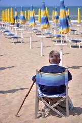 Uomo anziano seduto in spiaggia