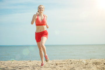Young lady running at the sunny summer sand beach. Workout.  Jog
