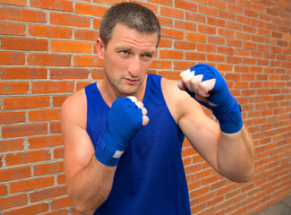 boxer in blue bandage on brick wall background