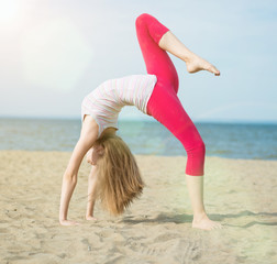 Young lady practicing yoga. Workout near ocean sea coast.