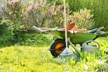 Gartengeräte und Schubkarre im Garten