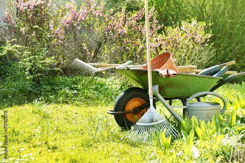 canvas print picture Gartengeräte und Schubkarre im Garten