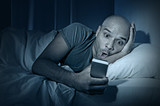 young internet addict man in bed using mobile phone poster
