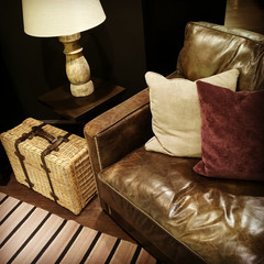Leather sofa, lamp and rattan suitcase