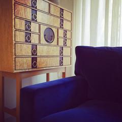 Wooden dresser and blue velvet armchair