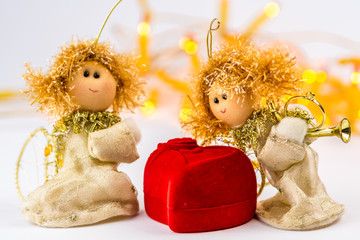 two Christmas angels and red velvet heart on white background