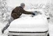 Mann befreit sein Auto vom Schnee