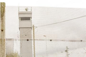 Blick durch den Grenzzaun auf einen Wachturm