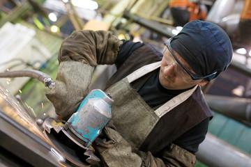 Industrial worker grinding metal sheet with sparks in workshop