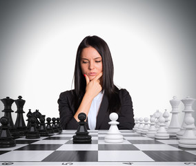 Lost in thought woman looking at chess board