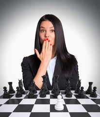 Surprised businesswoman looking at camera. Chessboard with chess
