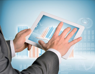 Man hands using tablet pc. Image of wire-frame buildings and