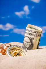 Sea shells compass and dollar money on  sand