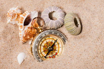 Sea  shells and  compass   on  sand