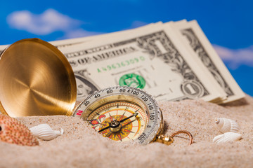 Sea  shells   compass  and dollar money on  sand