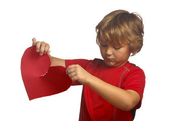Sad young boy in red holding torn broken heart