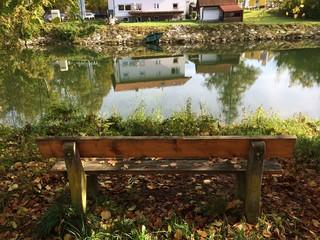 Parkbank im Herbst mit Blick auf Loisach