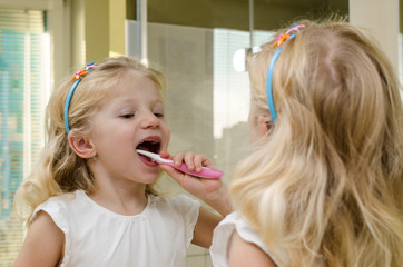 blond girl brushing teeth