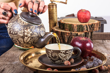 Woman pouring tea from teapot on vintage wooden table