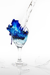 Blue water spill from a broken wine glass on white background