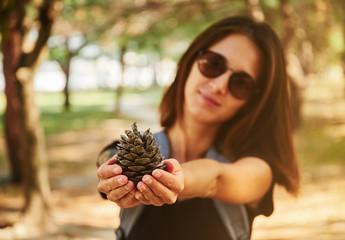 Woman showing a fir cone