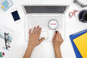 Woman hand is holding magnifying on keyboard button