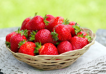 basket with strawberries on a garden wooden table