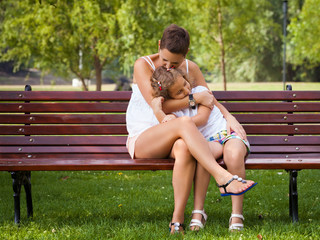 Mother and her little daughter sitting on the bench