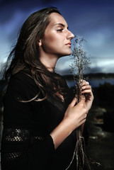 Cult woman by night with dry sprig of plant