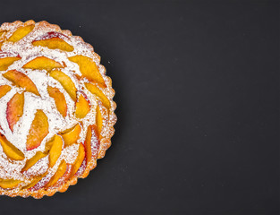 Peach pie with sugar powder on dark with a space for your iscrip