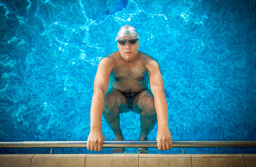 male athlete holding on edge of swimming pool and preparing to s