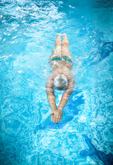 man in goggles swimming under water at swimming pool