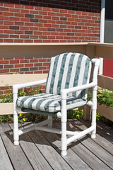 A generic PVC constructed lawn chair on a wood deck