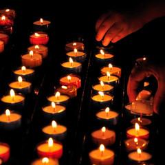 Deux mains allument des bougies dans un église