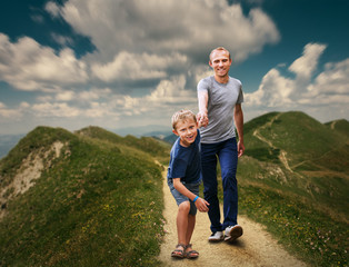 Father  and Son walking on the highmountain footpath;